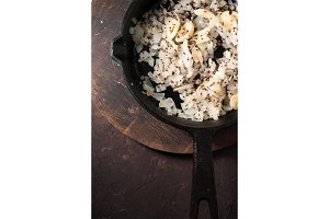 Fried onions, garlic and mustard seeds in a cast-iron frying pan free space. Indian food
