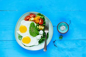Fried eggs, avocado and vegetables