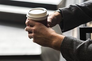 Person holding hot coffee cup