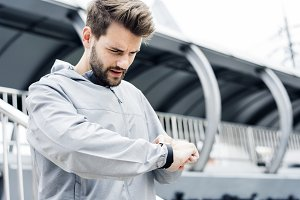 Sporty man looking at his smartwatch