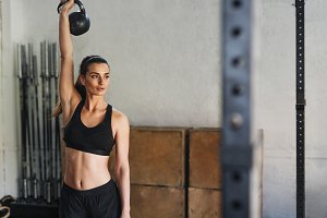 Young woman lifting kettlebell
