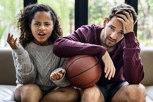 Young couple watching basketball