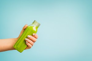 Hand with green smoothie or juice