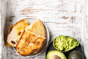 Pieces of toasted white sourdough bread and ripe avocado