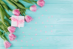 Pink tulips, gift and paper hearts