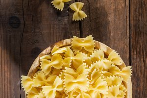 Raw Pasta Farfalle in Wooden Bowl