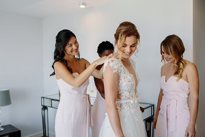 Bridesmaids preparing bride