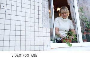 Woman in open window planting  house