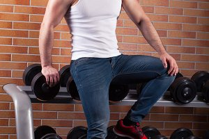 Muscular man stands near the counter with dumbbells in the gym.