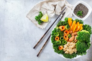 Healthy vegan buddha bowl with kale leaves and raw vegetables