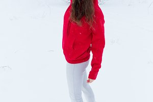 A young woman in a blank blue sweater and jeans shorts stands against the winter background