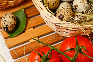 Quail eggs in basket. Tomato.