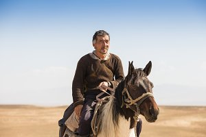 Normal steppe groom, who is tending the horses in Kazakhstan