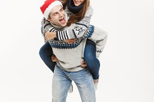 Christmas Concept - Full-length Young happy couple in sweaters enjoying piggyback ride isolated on white grey background
