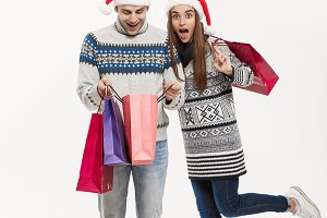 Christmas Concept - Full length Young attractive couple holding shopping bags isolated on white grey background.