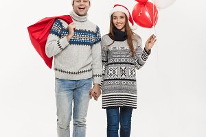 Christmas Concept - Full length Young attractive couple holding santa bag and balloon isolated on white grey background.