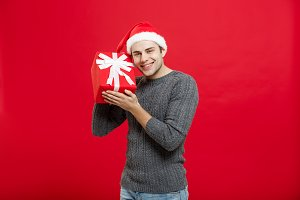 Christmas Concept - handsome young man in sweater with red christmas gift