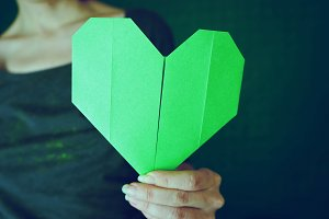 Young woman holding a green heart