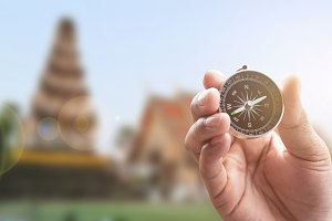 compass in hand on thai temple blur