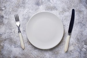 Empty plate and silverware on concrete table