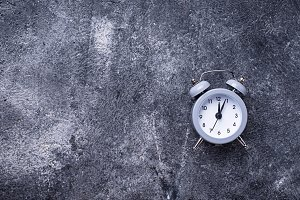 Grey vintage alarm clock on concrete table