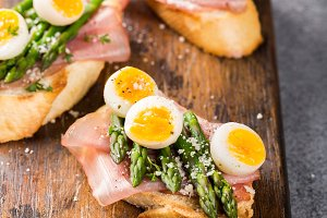 Fresh sendwich with ham, asparagus and quail eggs