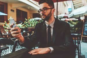 Businessman with smartphone in cafe