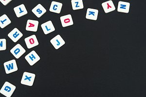 English colored square letters scattered on black background