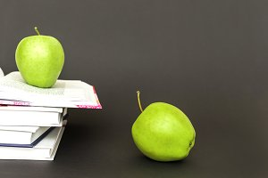 Two green apples and open books