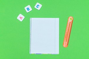 Letter blocks alphabet ABC with notebook and ruler on green background