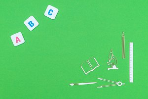 Overhead school supplies and letters abc on green background