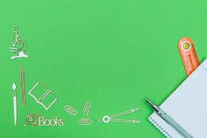 School supplies wooden miniatures and notebook with ruler and pen on green background
