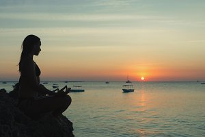 Young woman practicing yoga sunset