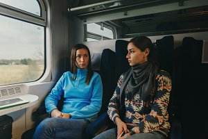 Two girlfriends traveling by train