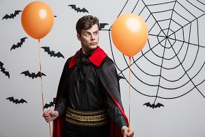 Portrait of handsome caucasian in Vampire halloween costume with colorful Balloon.