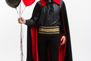 Full-lenght Portrait of handsome caucasian Vampire in black and red halloween costume.