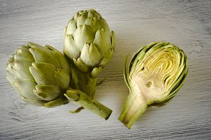 Fresh green artichokes cut on aged w