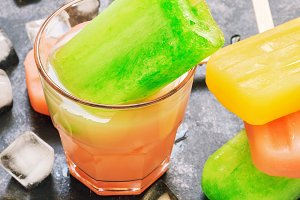 Popsicles in a glass with juice.