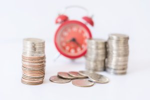 coins front of blur red alarm clock