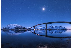 Bridge and starry sky with reflection in water
