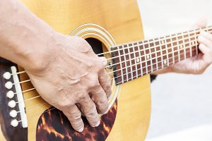 Hand of old man on playing guitar