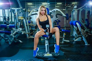 Brutal fitness sexy woman with a muscular in the gym. Sports and fitness - concept of healthy lifestyle. Fitness woman in the gym. Sits with a dumbbell