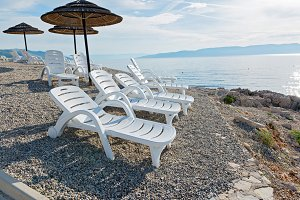 Pebble beach with chaise-longues and umbrellas