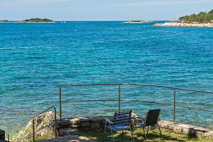 Rocky beach with two chairs in Istria