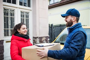 Woman receiving parcel from delivery man at the door.