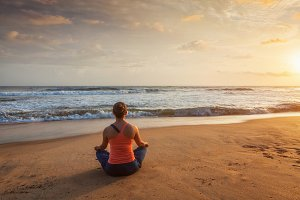 Woman doing yoga Lotus pose oudoors at beach