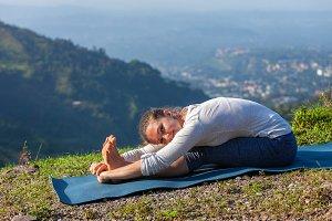 Woman doing yoga asana Paschimottanasana forward bend