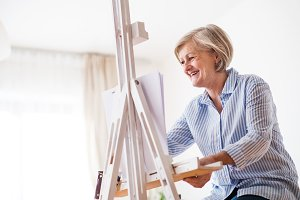 A senior woman painting at home.