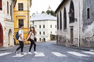 Two young tourists crossing the road in the old town.