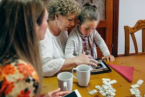 Grandmother and granddaughter play a game on the tablet